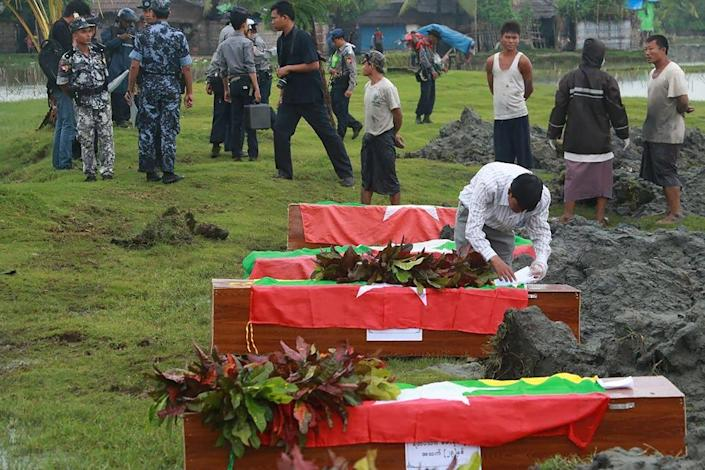 Myanmar border police prepare flag-draped coffins with bodies of border guards killed in mysterious raids, during a funeral ceremony at a cemetery in Maungdaw, western Rakhine state, on October 11, 2016 (AFP Photo/Khine Htoo Mrat)