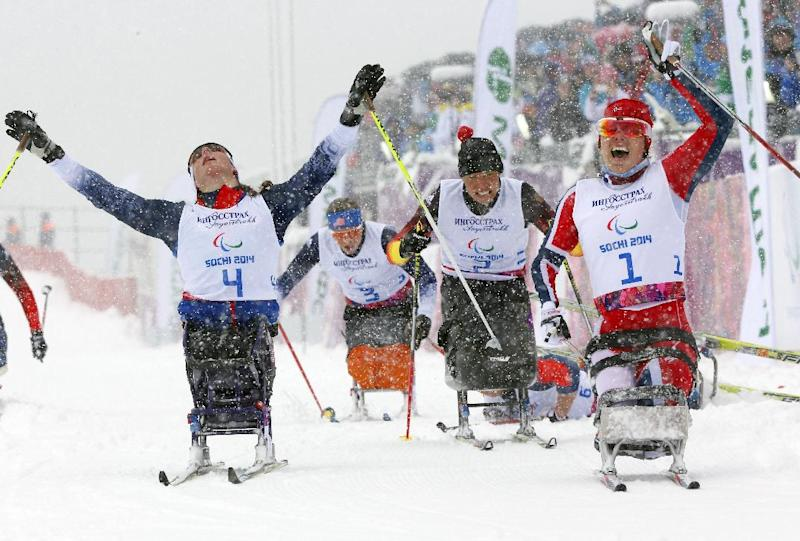 Mariann Marthinsen, right, of Norway, celebrates her gold medal as Tatyana Mcfadden, left, of the United States, reacts to her second-place finish in the finals of the women's cross country 1km sprint, sitting event at the 2014 Winter Paralympic, Wednesday, March 12, 2014, in Krasnaya Polyana, Russia. (AP Photo/Dmitry Lovetsky)