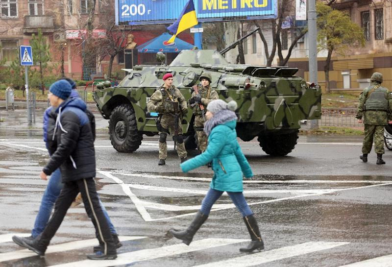 Ukrainian troops guard a polling station in Mariupol, in the Donetsk region, on November 29, 2015, as voters cast ballots in a local election that was put off when a nationwide October 25 poll was scrapped in the strategically important port city