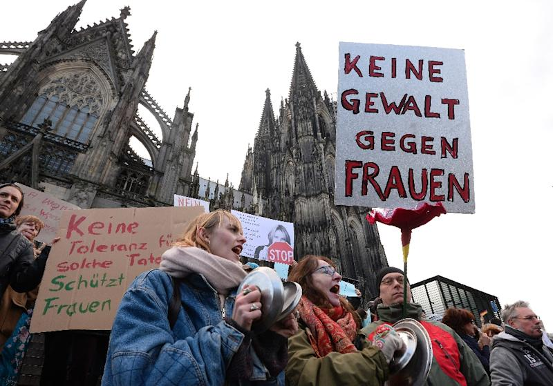 "A man holds up a sign reading ""No violence against women"" as he takes part in a demonstration outside Cologne cathedral in western Germany, on January 9, 2015 (AFP Photo/Roberto Pfeil)"
