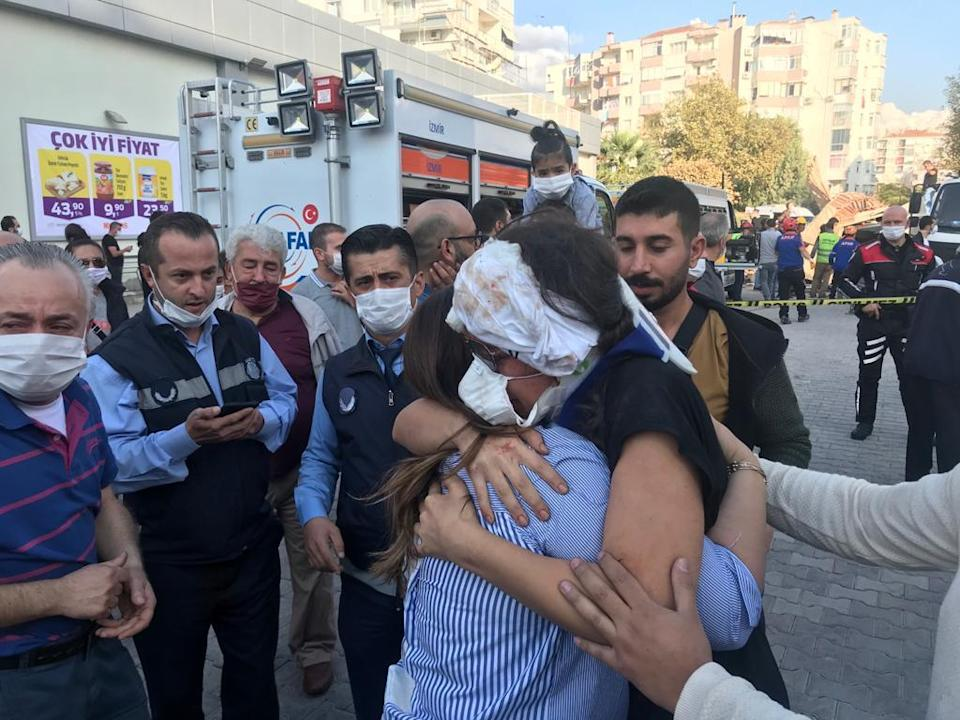 IZMIR, TURKEY - OCTOBER 30: A wounded woman hug her relative after being rescued from debris of a building in Bornova district of Izmir after a magnitude 6.6 quake shook Turkey's Aegean Sea coast, in Izmir, Turkey on October 30, 2020. (Photo by Tezcan Ekizler/Anadolu Agency via Getty Images)