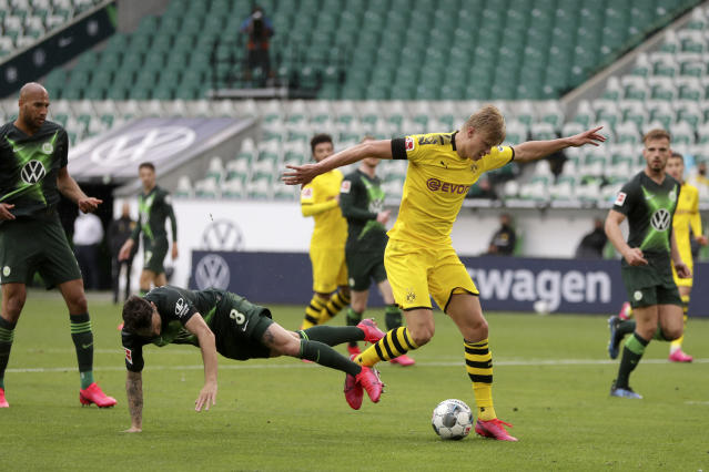 Wolfsburg's Renato Steffen, center left, fights for the ball with Dortmund's Erling Haaland during the German Bundesliga soccer match between VfL Wolfsburg and Borussia Dortmund in Wolfsburg, Germany, Saturday, May 23, 2020. The German Bundesliga is the world's first major soccer league to resume after a two-month suspension because of the coronavirus pandemic. (AP Photo/Michael Sohn, Pool)