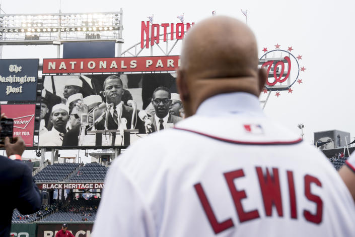 Rep. John Lewis, D-Ga., watches a video of himself before throwing out the ceremonial first pitch for Jackie Robinson Day before a baseball game between the Washington Nationals and the Colorado Rockies at Nationals Park on April 15, 2018, in Washington. (Photo: Andrew Harnik/AP)