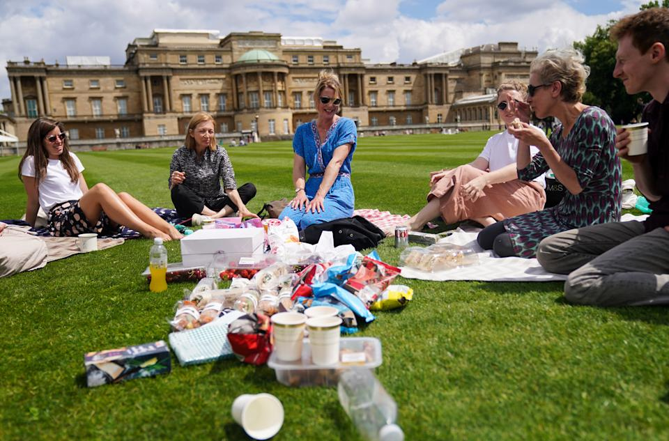 Visitors enjoy a picnic on the lawn during a preview of the Garden at Buckingham Palace, Queen Elizabeth II's official residence in London, which opens to members of the public on Friday. Visitors will be able to picnic in the garden and explore the open space for the first time. Picture date: Thursday July 8, 2021. (Photo by Kirsty O'Connor/PA Images via Getty Images)