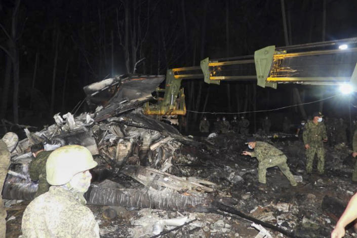 In this photo released by the Joint Task Force - Sulu, military soldiers search beside the remains of a Philippine military C-130 plane that crashed in Patikul town, Sulu province, southern Philippines, Sunday July 4, 2021. Philippine troops found the last five dead from the crash of the transport aircraft in the south, raising the death toll to 50 in the military's worst air disaster, officials said Monday. (Joint Task Force-Sulu via AP)