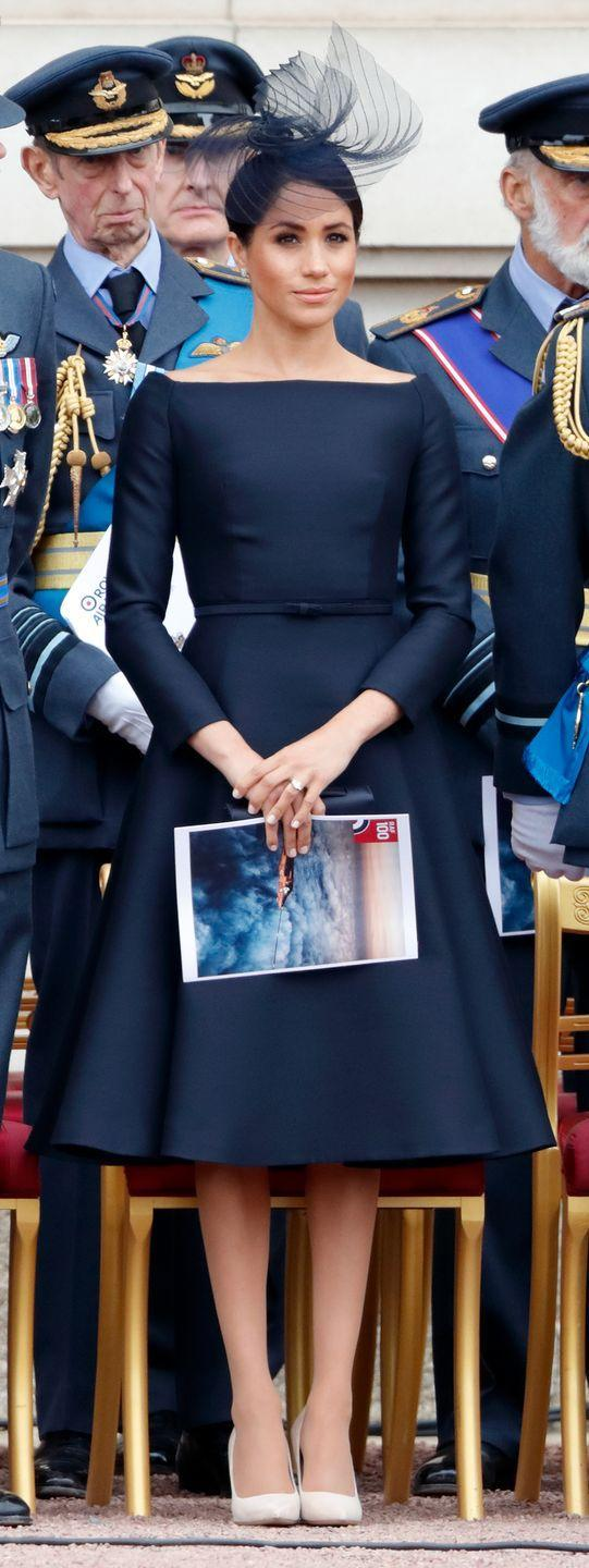 """<p>To celebrate the Royal Air Force's 100th anniversary, the royal wore a <span class=""""redactor-unlink"""">bespoke Dior look</span> black dress with a boat-cut neckline similar to her Givenchy wedding gown earlier this year, July 2018. </p>"""