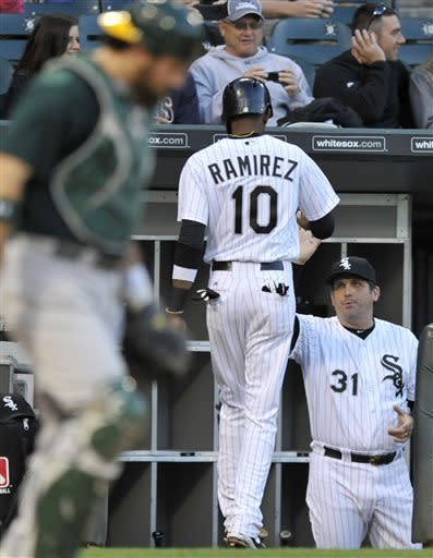 CORRECTS TO WHITE SOX HITTING COACH JEFF MANTO (31) NOT MANAGER ROBIN VENTURA (23) - Chicago White Sox hitting coach Jeff Manto (31) congratulates Alexei Ramirez (10) after Ramirez scored on an Alex Rios single during the third inning of a baseball game against the Oakland Athletics in Chicago, Thursday, June 6, 2013. (AP Photo/Paul Beaty)