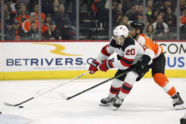 New Jersey Devils' Blake Coleman, left, is harassed by Philadelphia Flyers' Matt Niskanen as he tries to get a shot on goal during the first period of an NHL hockey game Wednesday, Oct. 9, 2019, in Philadelphia. (AP Photo/Tom Mihalek)