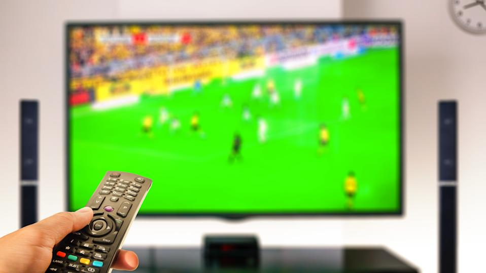 watching soccer at home tv with remote control on hand