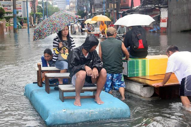 A Filipino commuter is being transported using a makeshift boat amid waist deep floodwaters in Makati City, south of Manila Philippines, 07 August 2012. Floodwaters triggered in many thorough fares in Metro Manila and nearby provinces after an overnight heavy rainfall brought by a southwest monsoon, which caused cancellation of classes in all levels in Metro Manila and operations of government offices. (Rey Cedilla, NPPA Images)