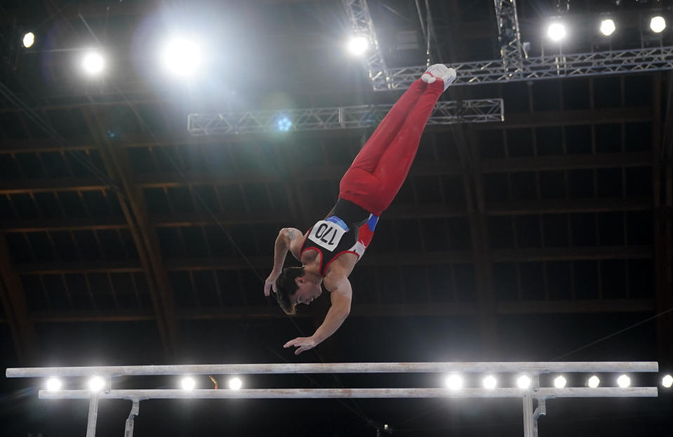 The Russian Olympic Committee's Artur Dalaloyan performs on the parallel bars during the men's artistic gymnastic qualifications at the 2020 Summer Olympics, Saturday, July 24, 2021, in Tokyo. (AP Photo/Gregory Bull)