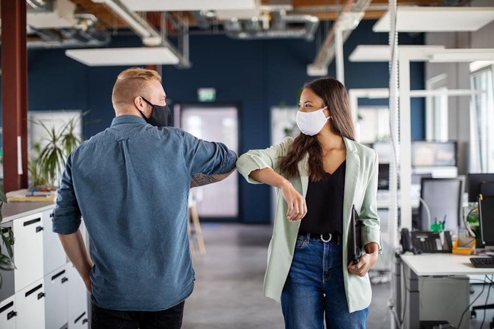Two business colleagues greeting with elbow in office. Business people bump elbows in office for greeting during covid-19 pandemic.
