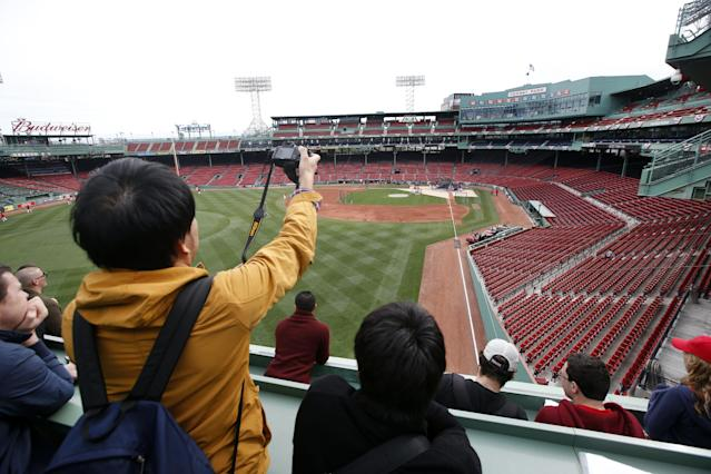 Fans on a tour of Fenway Park in Boston watch from the Green Monster seats as Boston Red Sox baseball players work out on Thursday, Oct. 10, 2013 in preparation for Game 1 of the AL championship series on Saturday. (AP Photo/Elise Amendola)