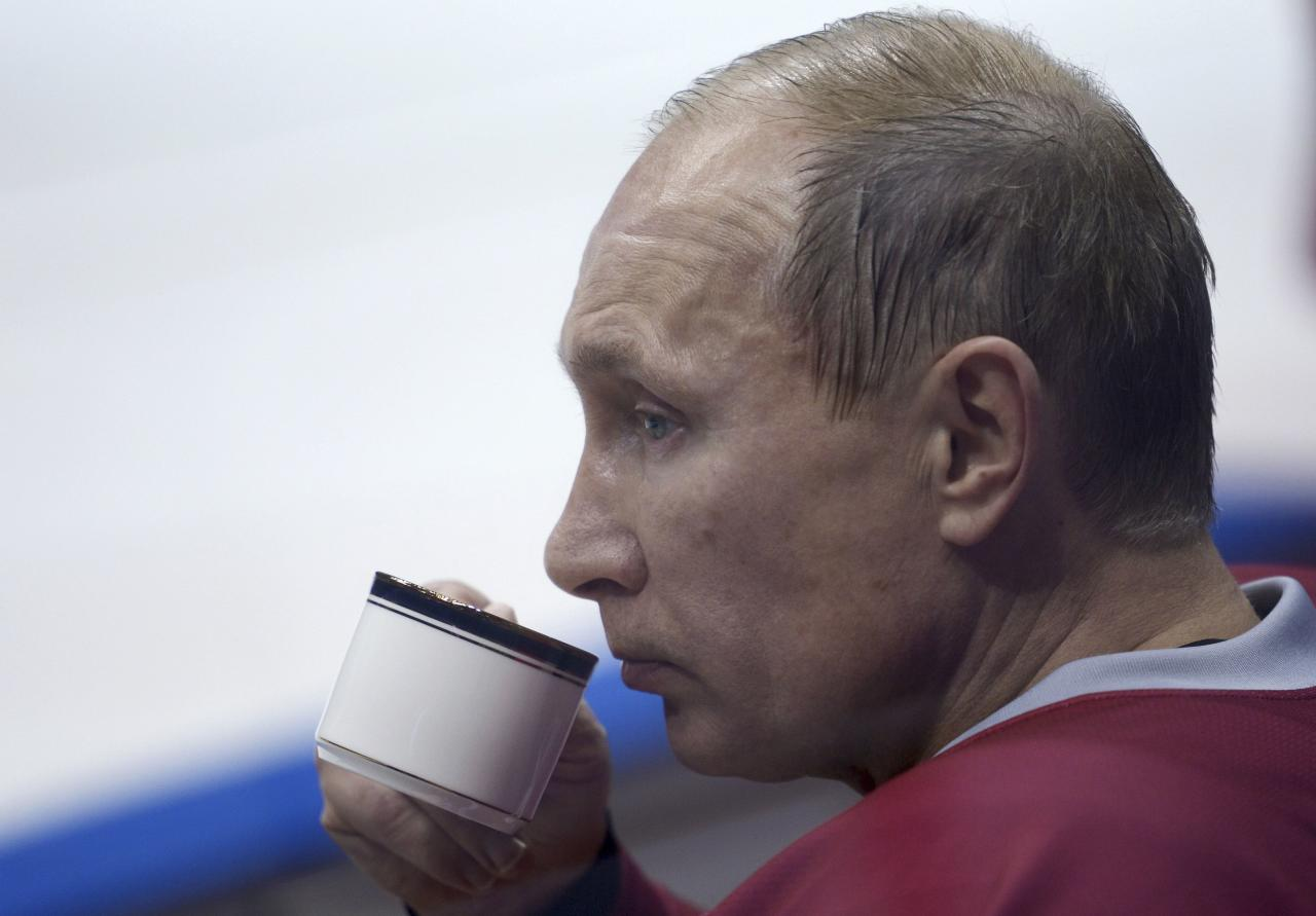 Russian President Putin drinks from a cup during a friendly ice hockey match in the Bolshoi Ice Palace near Sochi