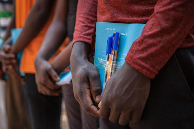 <p>Newly released child soldiers receive school supplies as part of a re-integration kit which includes clothing and mosquito nets during a release ceremony for child soldiers in Yambio, South Sudan on Feb. 7, 2018. (Photo: Stefanie Glinski/AFP/Getty Images) </p>