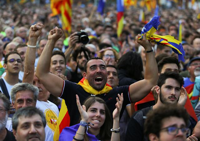 Crowds watching a giant screen showing events inside the Catalan Parliament. (Photo: Ivan Alvarado/Reuters)