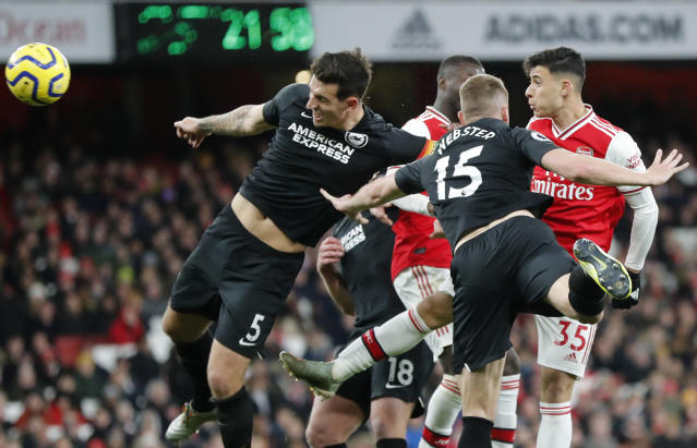 Brighton's Lewis Dunk, left, fights for a header during the English Premier League soccer match between Arsenal and Brighton, at the Emirates Stadium in London, Thursday, Dec. 5, 2019. (AP Photo/Frank Augstein)