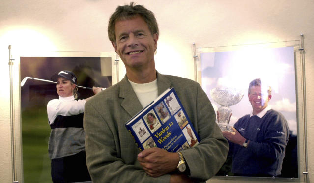 FILE - In this Aug. 21, 2003 file photo Alastair Johnston, vice chairman of IMG, poses outside his office with one of his books in Cleveland. Johnston has the largest collection of golf books in the world, and he' s gifting it to the R&A. (AP Photo/Jamie-Andrea Yanak, file)