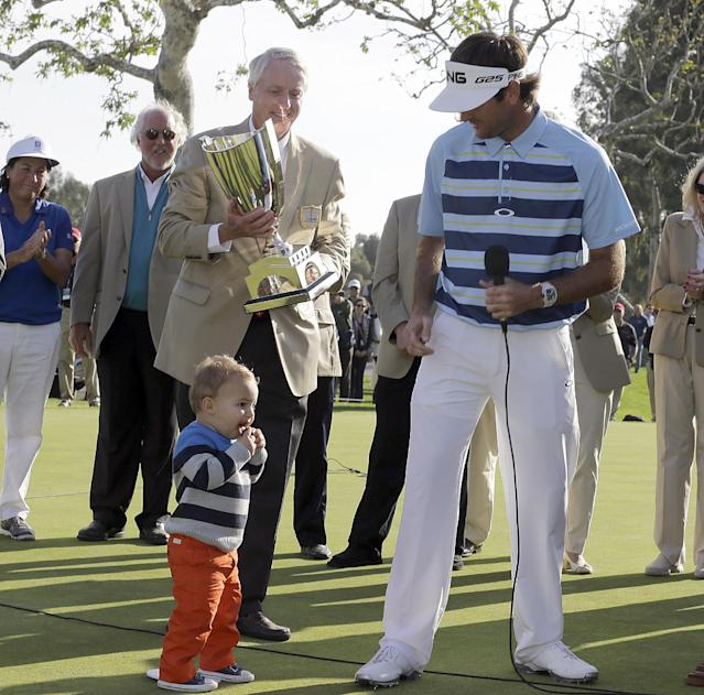 Bubba Watson is joined by his son Caleb at the ceremony after his victory in the Northern Trust Open golf tournament at Riviera Country Club in the Pacific Palisades area of Los Angeles, Sunday, Feb. 16, 2014. Watson carded a 15-under-par 269, two strokes ahead of the second-place finisher. (AP Photo/Reed Saxon)