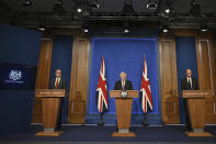 Britain's Prime Minister Boris Johnson, center, speaks during a media briefing on coronavirus in Downing Street, London, Monday, July 5, 2021. Johnson says people in England will no longer be required by law to wear face masks in indoor public spaces and to keep at least 1 meter (3 feet) apart as soon as later this month. Johnson on Monday confirmed plans to reopen society despite rising coronavirus cases. (Daniel Leal-Olivas/Pool Photo via AP)