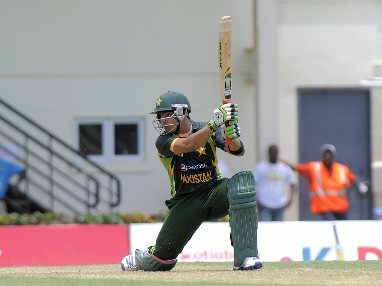 Pakistan batsman Umar Akmal on his way to 40 not out during the 3rd ODI West Indies v Pakistan at Beausejour Cricket Ground in Gros Islet on July 19, 2013. The wicket-keeper is Johnson Charles. Pakistan made 229-6 off their 50 overs in the third one-day international against the West Indies.    AFP PHOTO/Randy Brooks        (Photo credit should read RANDY BROOKS/AFP/Getty Images)