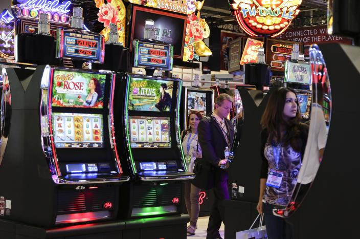 Gaming industry representatives stop to play various slot machines at the Global Gaming Expo, Wednesday, Sept. 25, 2013, in Las Vegas. Moving away from moving parts to video technology, the venerable slot machine is undergoing a generational shift and manufacturers are rolling out the first generation of joystick-controlled, penny arcade-themed gambling machines. (AP Photo/Julie Jacobson)