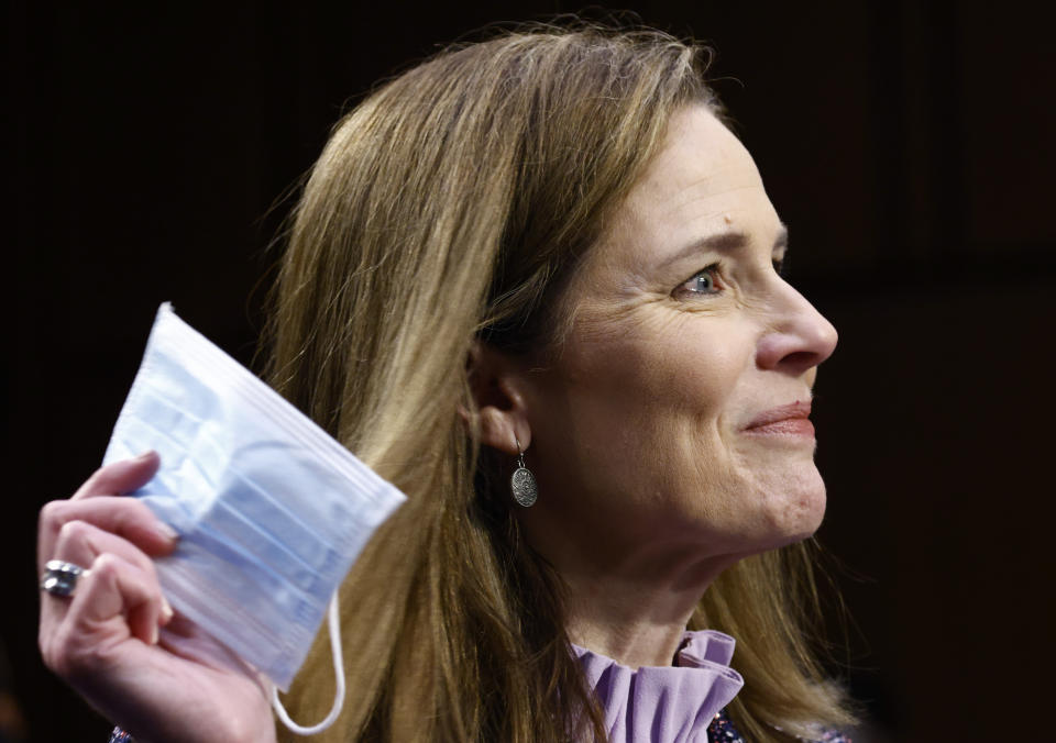 Supreme Court nominee Amy Coney Barrett holds a face mask up as she testifies during the third day of her confirmation hearings before the Senate Judiciary Committee on Capitol Hill in Washington, Wednesday, Oct. 14, 2020. (Photo by Samuel Corum/Getty Images)