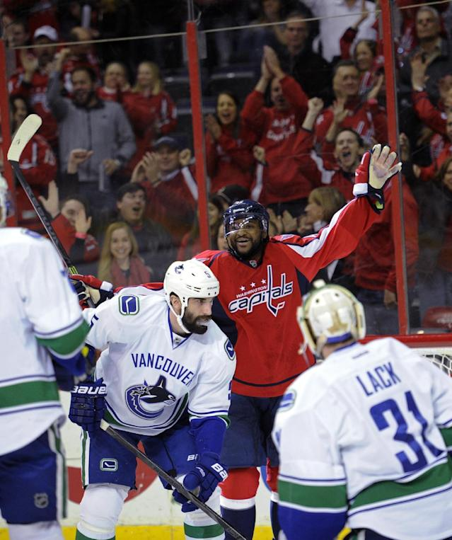 Washington Capitals right wing Joel Ward, back, celebrates his goal as Vancouver Canucks goalie Eddie Lack (31) and Jason Garrison (5) react during the first period of an NHL hockey game, Friday, March 14, 2014, in Washington. (AP Photo/Nick Wass)
