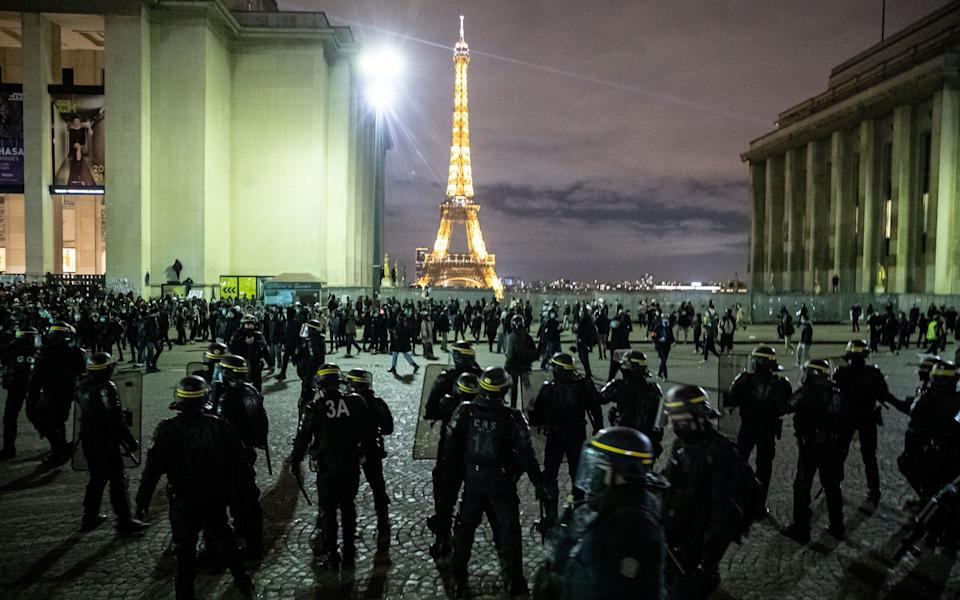 Riot police clear protesters gathered on Place du Trocadero near the Eiffel Tower  - Shutterstock