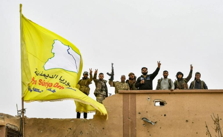 "Syrian Kurdish fighters raise their flag in March after overrunning the last vestige of the Islamic Strate group's ""caliphate"" in a US-backed offensive they had hoped would earn them Western support for their dreams of self-rule"