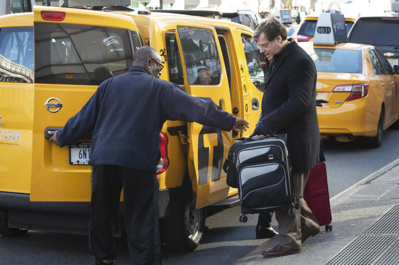 """A taxi driver helps a traveler with his suitcase, Wednesday, Jan. 29, 2020, in New York. A task force studying New York City's struggling taxi industry called Friday for """"mission-driven"""" investors to help bail out drivers who incurred massive debt once the value of the medallion that allows a person to operate a yellow cab plummeted in the age of Uber and Lyft. (AP Photo/Mark Lennihan)"""