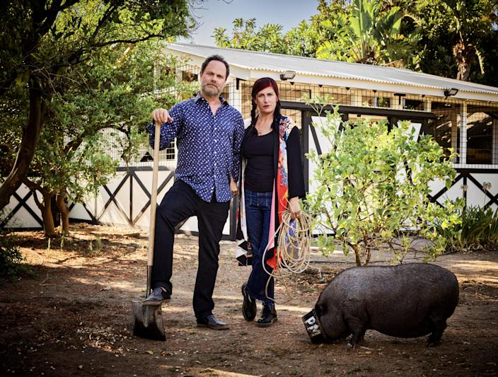 "<div class=""caption""> Wilson and Reinhorn strike an <em>American Gothic</em> pose by the barn. Amy, one of the couple's two pigs, remains ever vigilant for snacks. </div>"