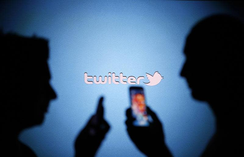 Men are silhouetted against a video screen with a Twitter logo as they pose with Samsung S3 and S4 smartphones in this photo illustration taken in the central Bosnian town of Zenica, August 14, 2013. REUTERS/Dado Ruvic/Files