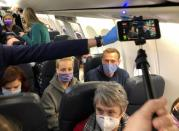 Russian opposition leader Alexei Navalny is seen on board a plane before the departure for Moscow at an airport in Berlin