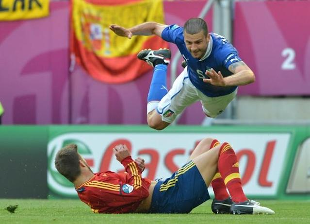 TOPSHOTS Italian midfielder Thiago Motta (top) falls over Spanish defender Gerard Pique during the Euro 2012 championships football match Spain vs Italy on June 10, 2012 at the Gdansk Arena. AFP PHOTO / GABRIEL BOUYSGABRIEL BOUYS/AFP/GettyImages