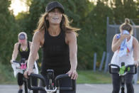 Jeanne Carter, co-owner of Fuel Training Studio, in Newburyport, Mass., front, works out on a stationary exercise bike during a spinning class in a parking lot outside the gym, Monday, Sept. 21, 2020, in Newburyport. The gym's revenue is down about 60% during the COVID-19 pandemic. Fuel Training Studio plans to continue holding outdoor classes into the winter with the help of a planned greenhouse-like structure with heaters but no walls. (AP Photo/Steven Senne)