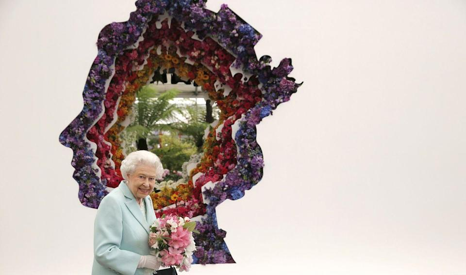 <p>The queen held a pink bouquet while she stood in front of a floral exhibit by the New Covent Garden Flower Market in London. </p>