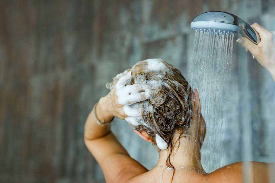 Back view of a woman washing her hair with a shampoo in bathroom. Copy space.