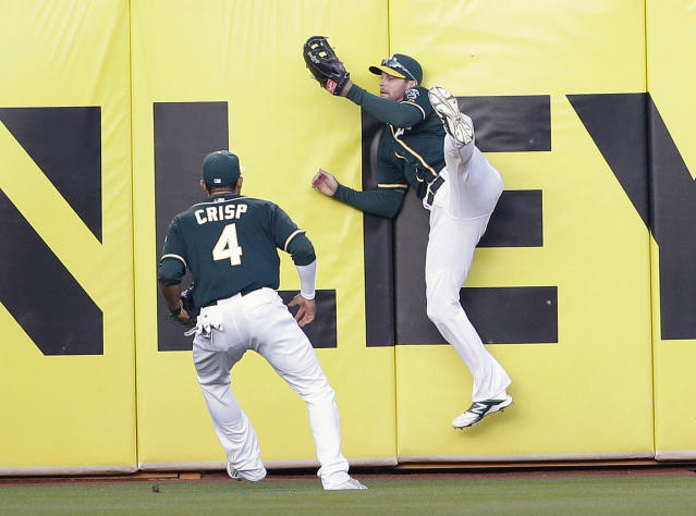 Oakland Athletics right fielder Craig Gentry, right, makes a leaping catch against the outfield wall on a pop fly by Seattle Mariners' Corey Hart as center fielder Coco Crisp (4) stands near during the first inning of a baseball game on Tuesday, May 6, 2014, in Oakland, Calif. (AP Photo/Marcio Jose Sanchez)