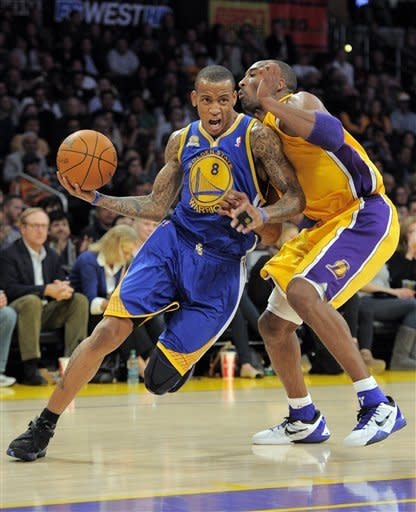 Golden State Warriors shooting guard Monta Ellis, left, powers by Los Angeles Lakers shooting guard Kobe Bryant during the first half of their NBA basketball game, Friday, Jan. 6, 2012, in Los Angeles. (AP Photo/Mark J. Terrill)