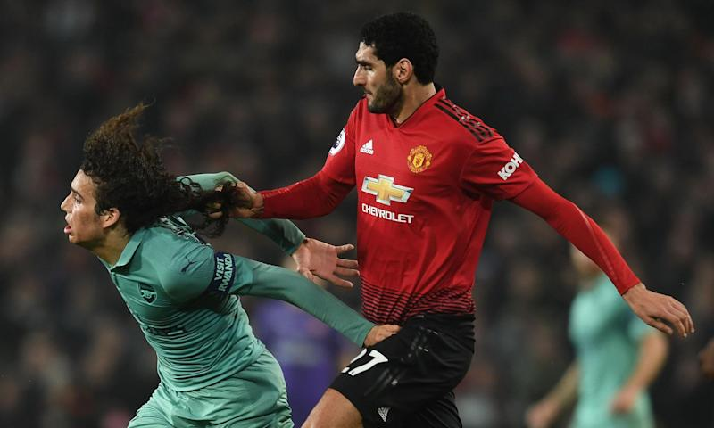 Arsenal's Mattéo Guendouzi has his hair pulled by Marouane Fellaini at Manchester United.