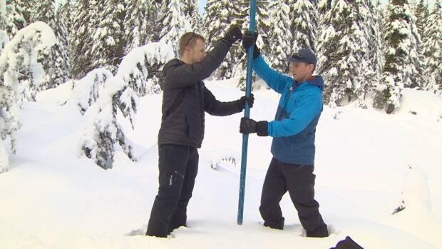Metro Vancouver field hydrologist Peter Marshall and CBC meteorologist Brett Soderholm push a snowpack measuring tool into the snow. New technology is helping provide a clearer picture of the region's drinking water supply.