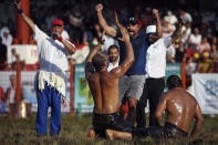 Wrestler Ali Gurbuz, center, celebrates after winning the final to gain the sport's golden belt in the 660th instalment of the annual Historic Kirkpinar Oil Wrestling championship, in Edirne, northwestern Turkey, Sunday, July 11, 2021. Thousands of Turkish wrestling fans flocked to the country's Greek border province to watch the championship of the sport that dates to the 14th century, after last year's contest was cancelled due to the coronavirus pandemic. The festival, one of the world's oldest wrestling events, was listed as an intangible cultural heritage event by UNESCO in 2010. (AP Photo/Emrah Gurel)