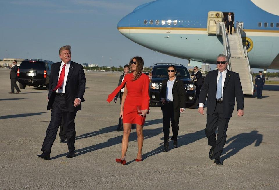 <p>The first lady matched her $2,095 red Givenchy cape dress with $595 Christian Louboutin flats to greet her husband and well-wishers at the airport. (Photo: Getty Images) </p>