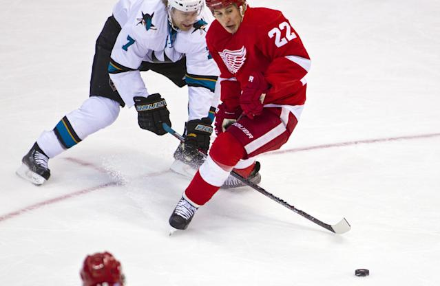 San Jose Sharks defenseman Brad Stuart (7) reaches for the puck with his stick between the legs of Detroit Red Wings forward Jordin Tootoo (22), during the second period of an NHL hockey game in Detroit, Mich., Monday, Oct. 21, 2013. (AP Photo/Tony Ding)