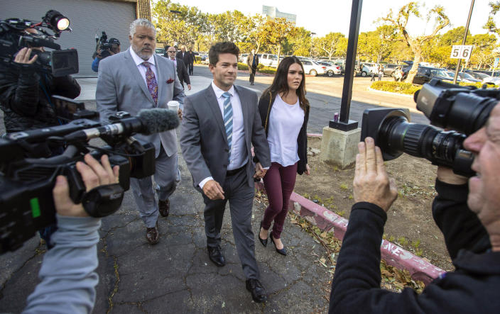 FILE - In this Friday, Feb. 7, 2020, file photo, Grant Robicheaux, center, and Cerissa Riley, arrive at Orange County Superior Court Harbor Justice Center in Newport Beach, Calif. State prosecutors want to drop most sex crime charges filed against a reality TV doctor and his girlfriend, who are accused of drugging and raping several women at their Southern California home. The attorney general's office, which took over the case last year, asked an Orange County judge on Friday, May 14, 2021, to drop charges involving six of seven alleged victims. (Mark Rightmire/The Orange County Register via AP, File)