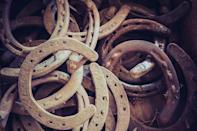 """<p>Horseshoes are considered symbols of good luck because of a Christian story about the 10th century saint Dunstan. He was a blacksmith who was approached by the Devil (in disguise) to put shoes on his horse but Dunstan saw through the disguise and put the shoes on the Devil's feet instead. Dunstan agreed to remove the shoes only if the Devil agreed never to try and enter a home with a horseshoe hanging on its door. It is customary to hang your horseshoe with seven nails, but there is <a href=""""https://www.livescience.com/33116-lucky-horseshoes.html"""" rel=""""nofollow noopener"""" target=""""_blank"""" data-ylk=""""slk:some debate"""" class=""""link rapid-noclick-resp"""">some debate</a> over whether they should be hung with the ends point up so the shoe catches luck or down so that the shoe pours luck onto everyone who passes through the doorway. </p>"""