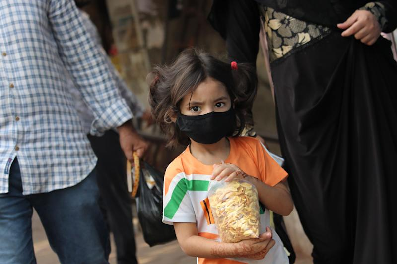 A girl wearing a protective face mask holds a bag of snacks during a curfew in response to the outbreak of the Coronavirus (COVID-19) pandemic on March 27, 2020 in Mumbai, India. (Photo by Himanshu Bhatt/NurPhoto via Getty Images)
