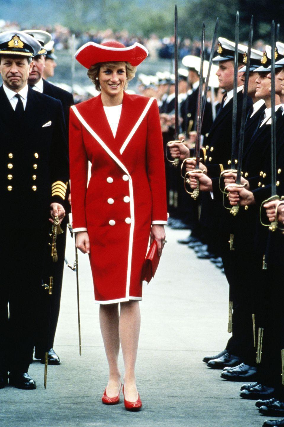 <p>In a red Catherine Walker dress and hat by Philip Somerville during a parade in Devon. </p>