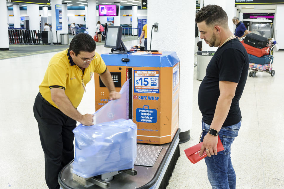A man getting his luggage wrapped by Secure Wrap at Miami International Airport. (Photo by: Jeffrey Greenberg/Universal Images Group via Getty Images)